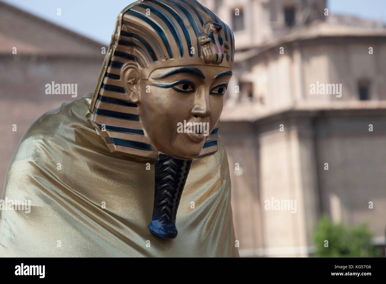 A performance artist dresses as an Egyptian Sphinx on the grounds of the Roman Forum in Rome, Italy - Stock Image