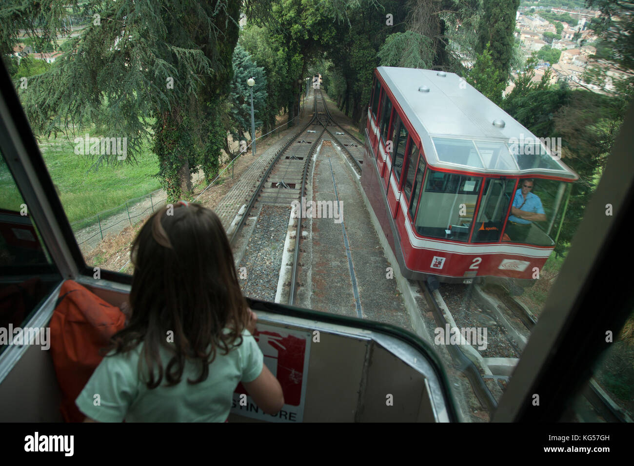 A young girl looks down the tracks of the Funicular in the Umbrian town of Orvieto, Italy. - Stock Image