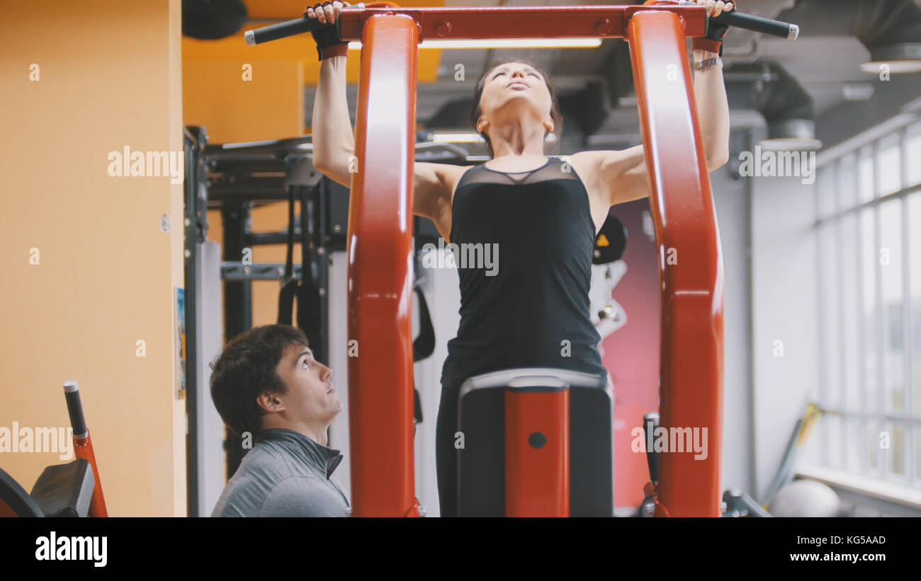 Fitness-club - young woman performs Pull-Ups with male coach - Stock Image