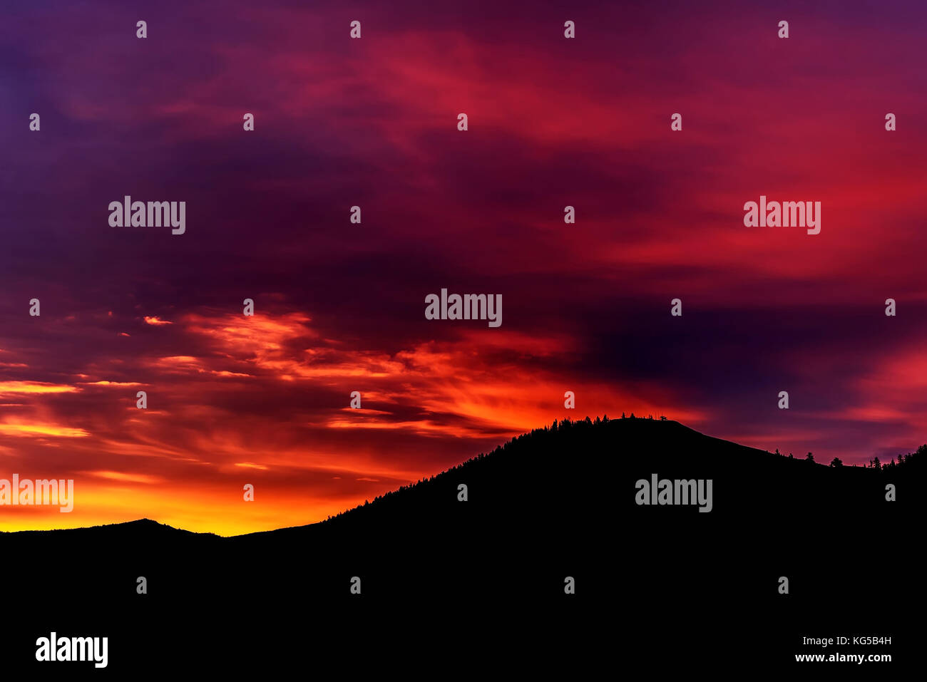 Colorful bright sunrise in yellow, orange, blue tones with clouds, illuminated by the rays of the sun in the sky Stock Photo
