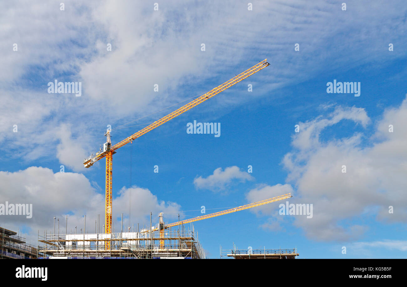 Two yellow tower cranes working on a construction site in a city centre. - Stock Image