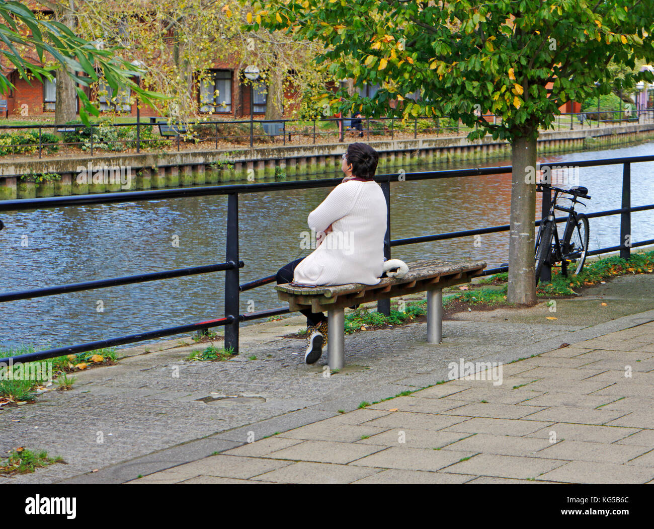 A middle aged woman sitting on a seat and staring out across a river. - Stock Image