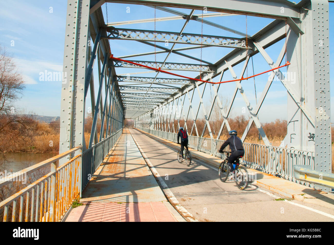 Two cyclists crossing the Iron Bridge. Titulcia, Madrid province, Spain. - Stock Image
