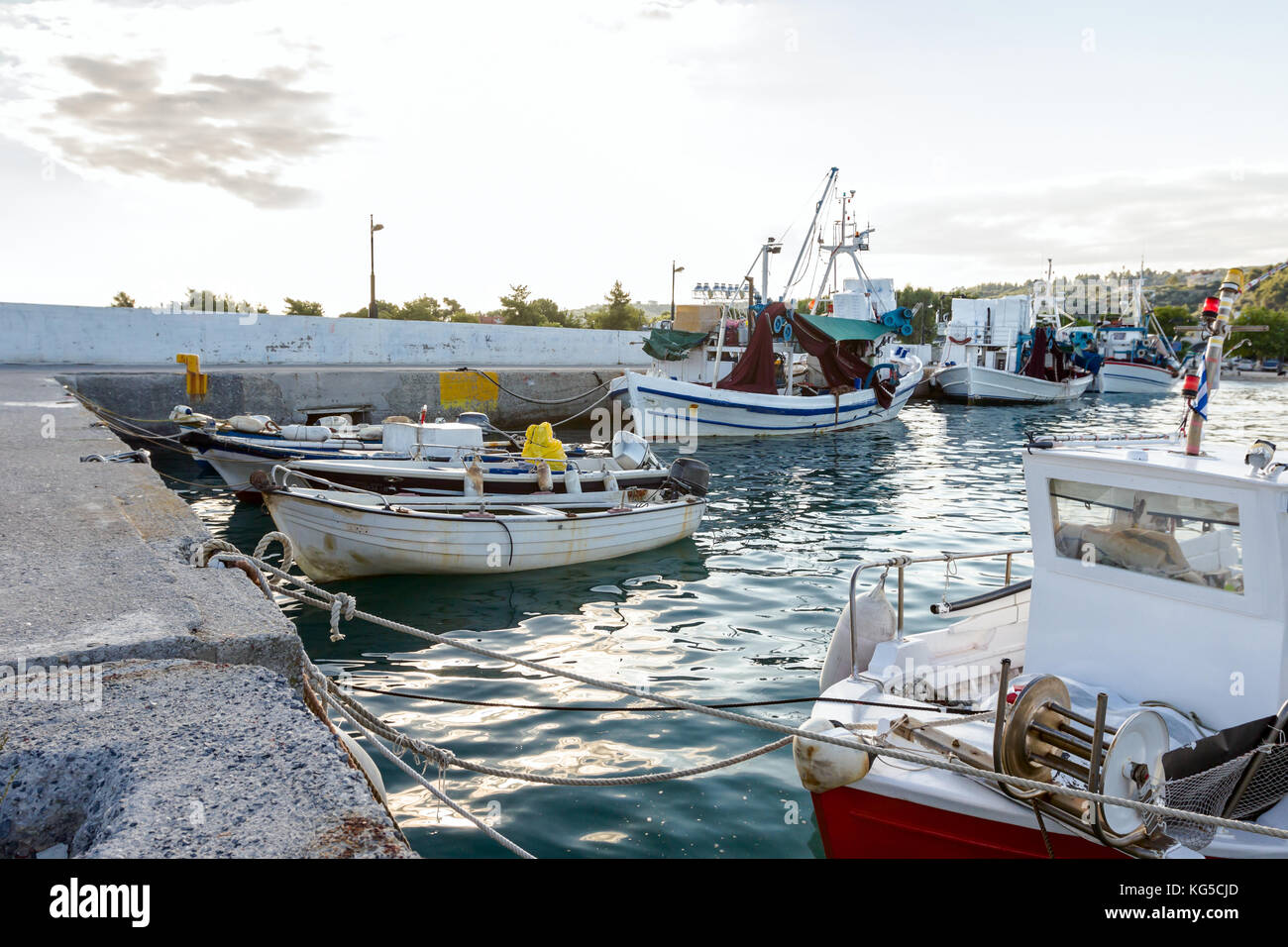 Docked colorful boats with fishing equipment are tied with ropes to the moor at the local port. Stock Photo
