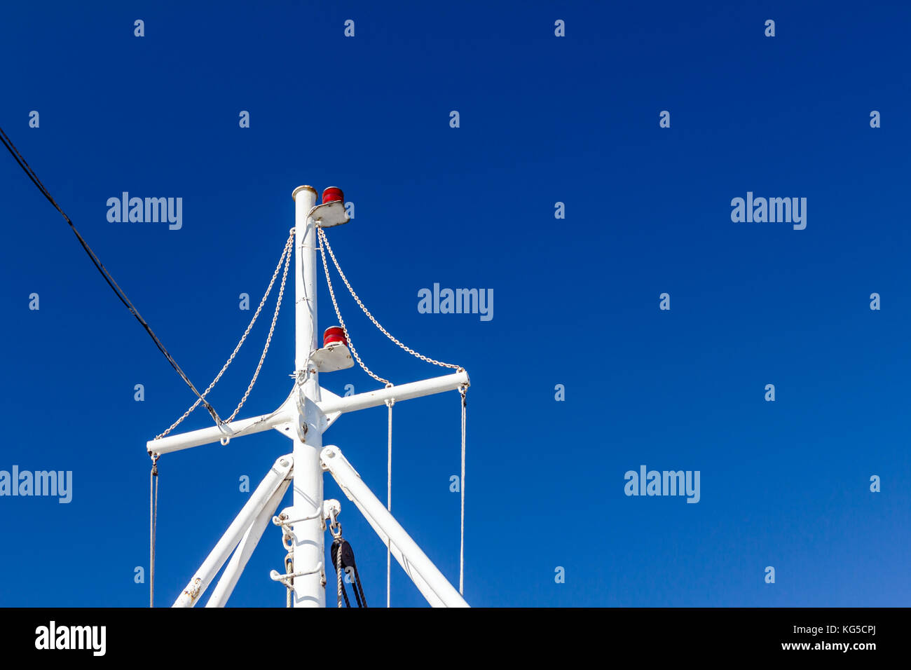 Tall white mast on sunny day with signalization lights. - Stock Image