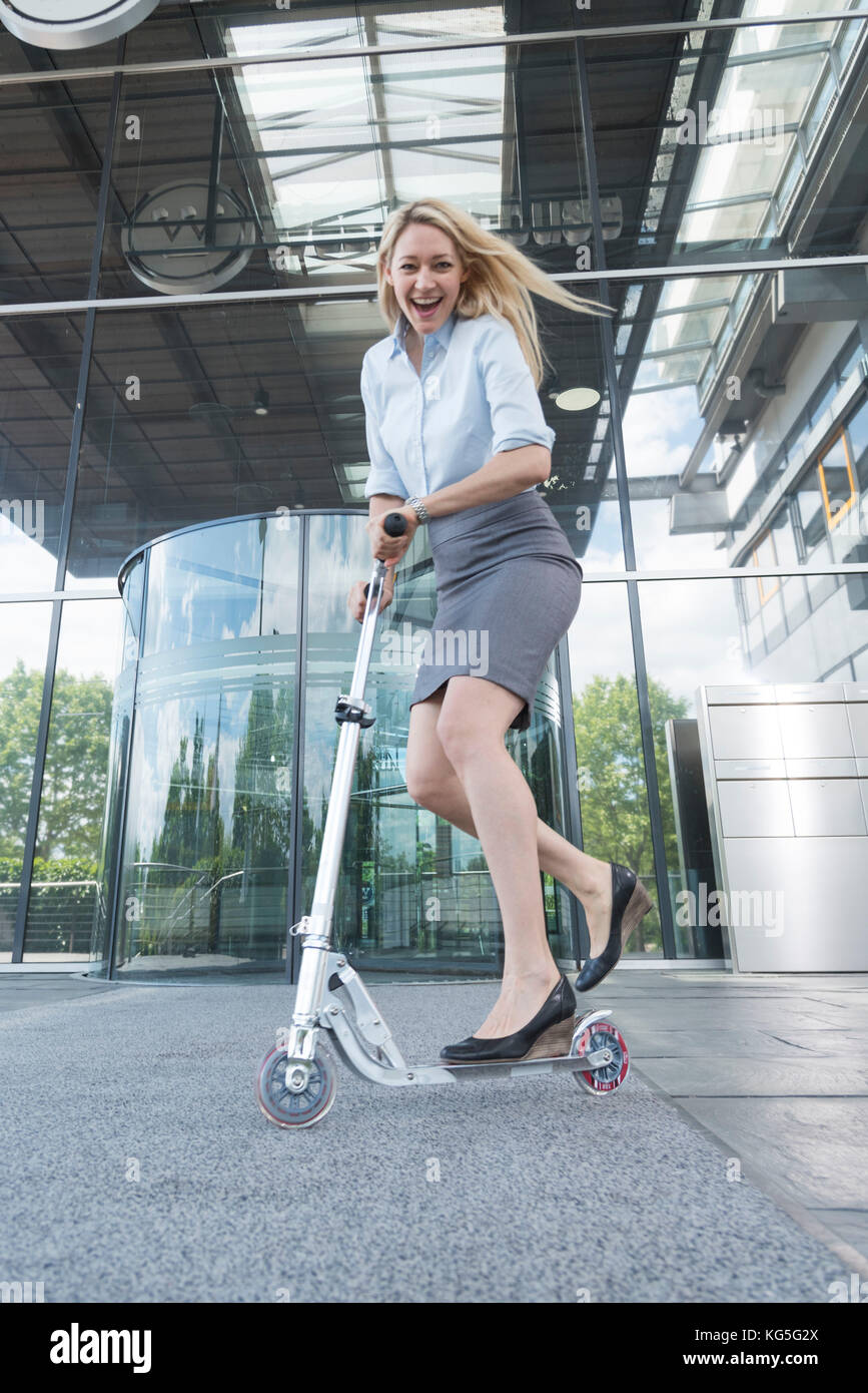 blond businesswoman drive laughingly a scooter - Stock Image