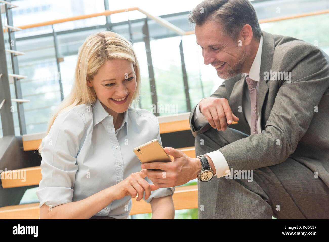Business people, man and woman with smartphone sit laughingly on stairs - Stock Image