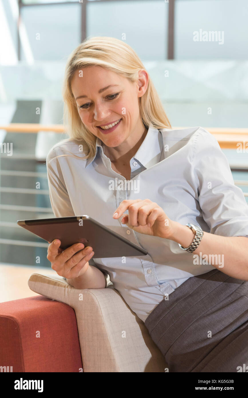Blond woman looks smilingly on her tablet - Stock Image