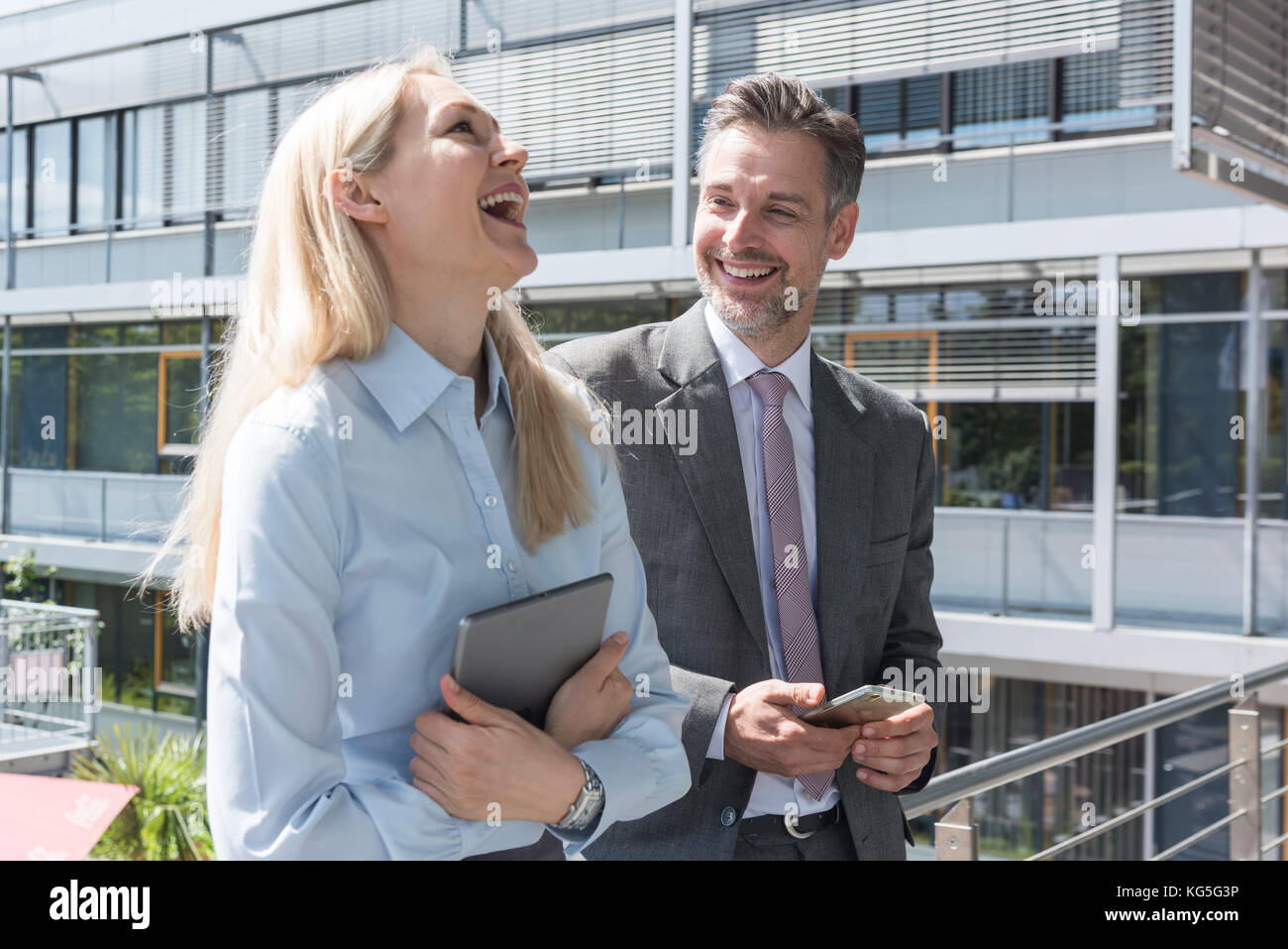 Businessman and businesswoman stand laughingly on a balcony in front of office - Stock Image