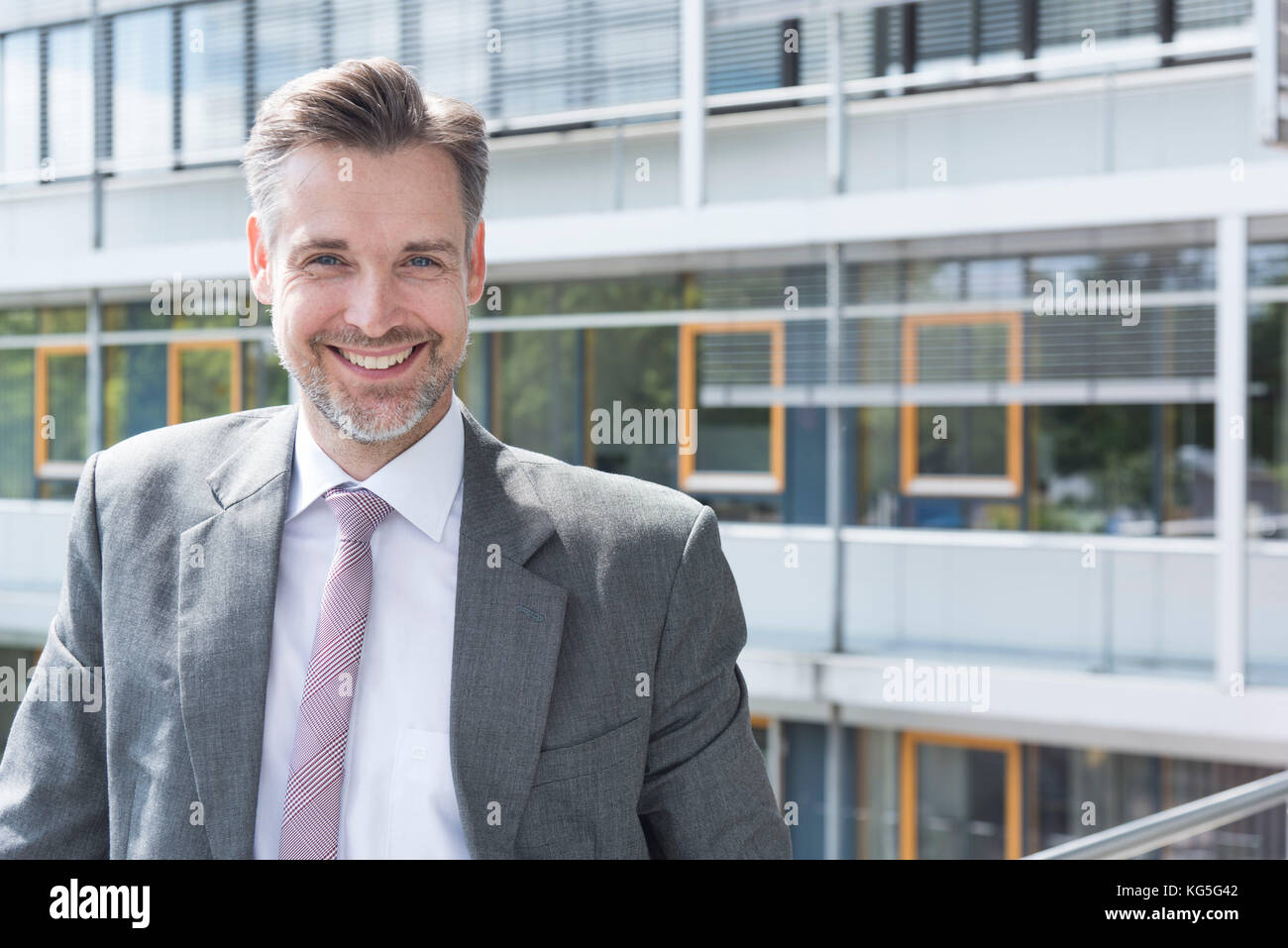 Businessman on balcony in front of office building, looks smilingly in the camera, portrait - Stock Image