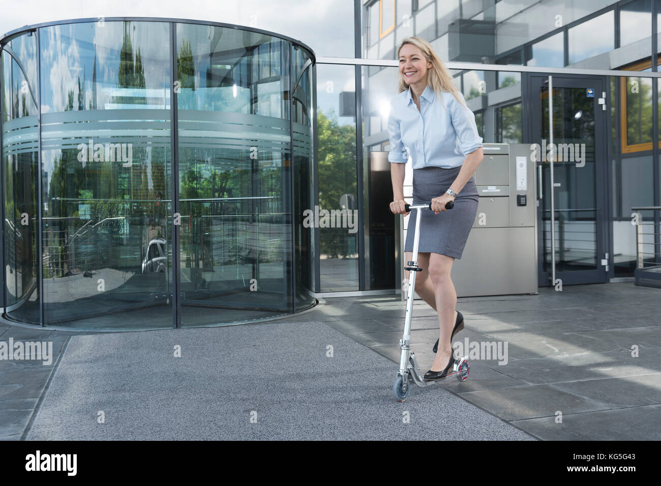 blond businesswoman with Scooter in front of entrance of an office building - Stock Image