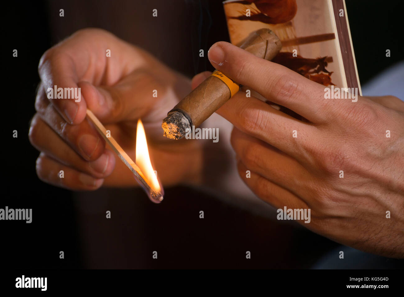 2 hands with cigar and burning match - Stock Image