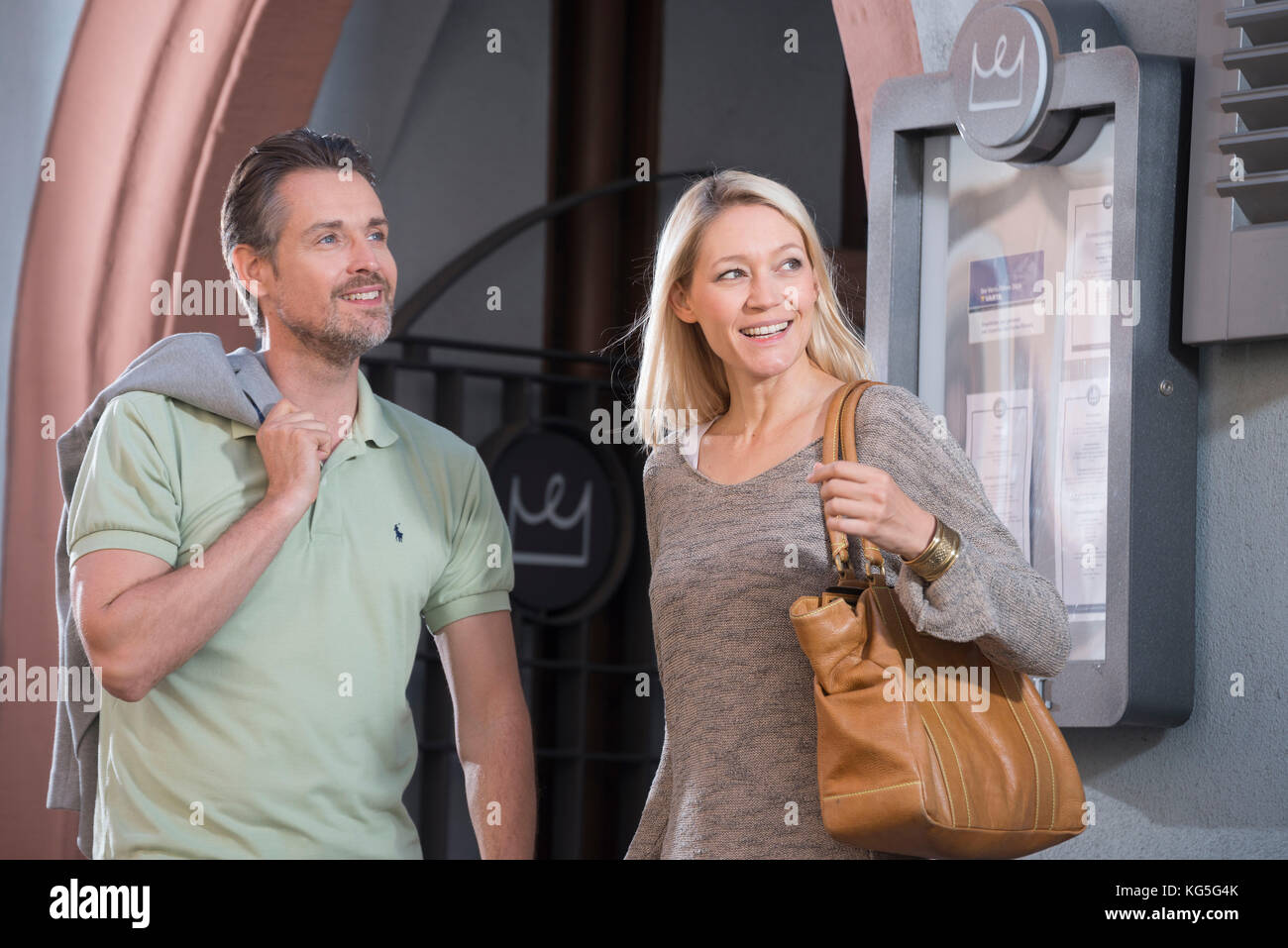 Man and woman stands smilingly in front of hotel input, portrait - Stock Image