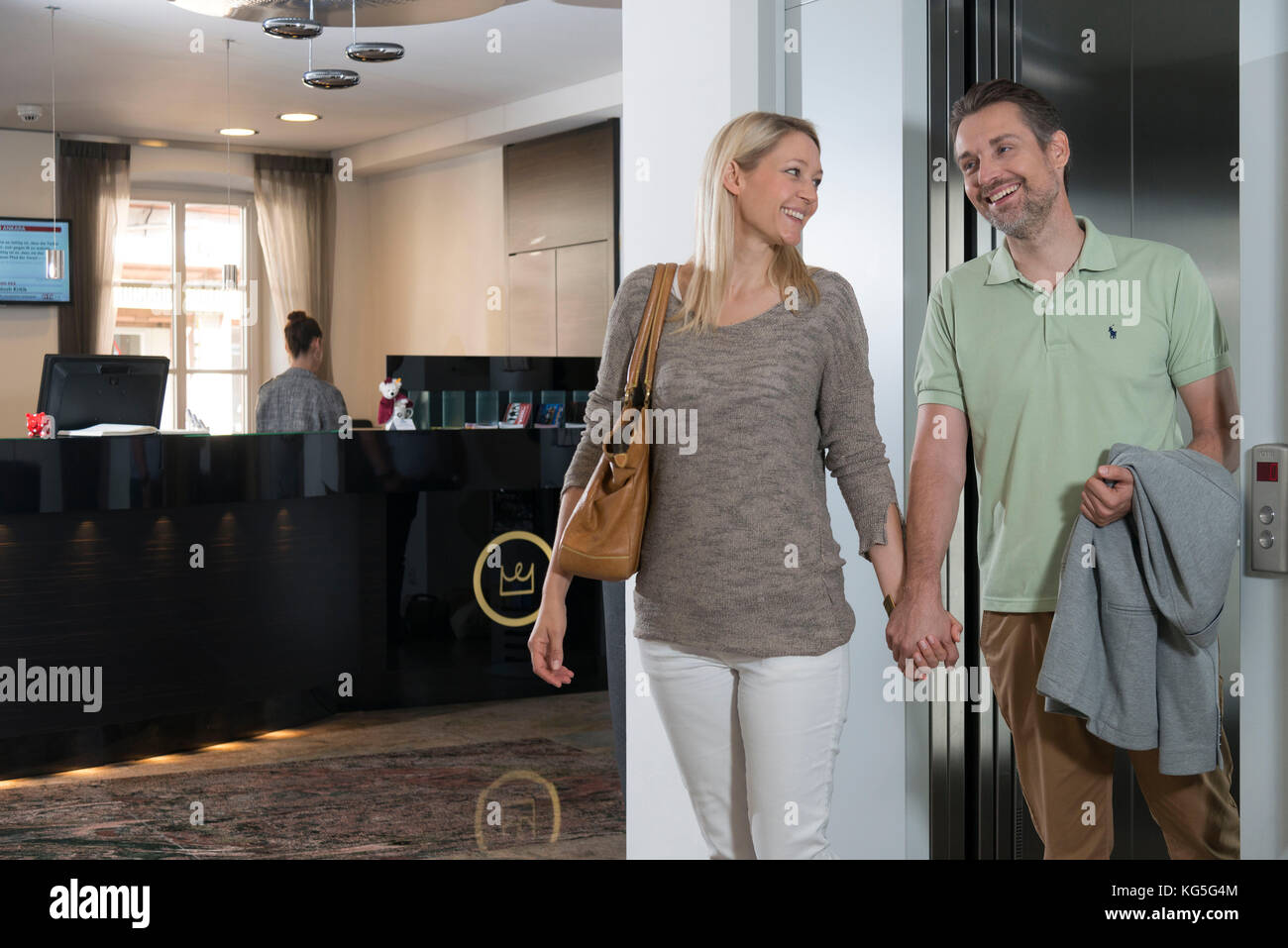 Couple comes laughingly out of the elevator in the hotel, hand in hand - Stock Image