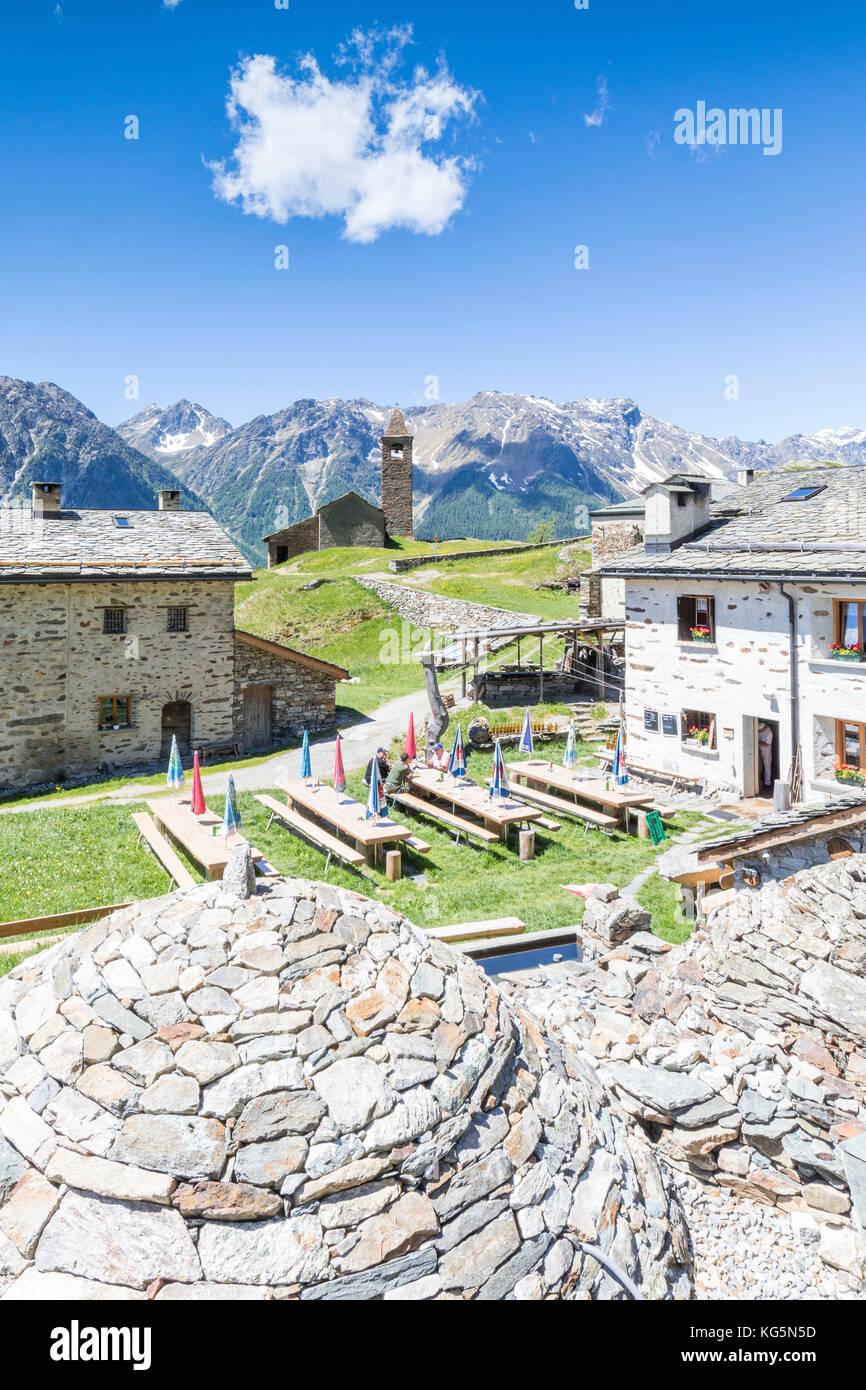 Mountain retreat and old stone caves called Crotto, San Romerio Alp, Brusio, Canton of Graubünden, Poschiavo - Stock Image