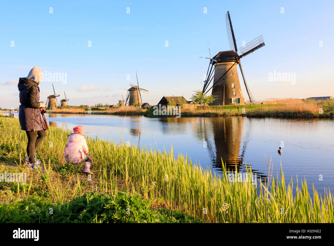 Mother and child admire the typical windmills reflected in the canal Kinderdijk Molenwaard South Holland The Netherlands Stock Photo