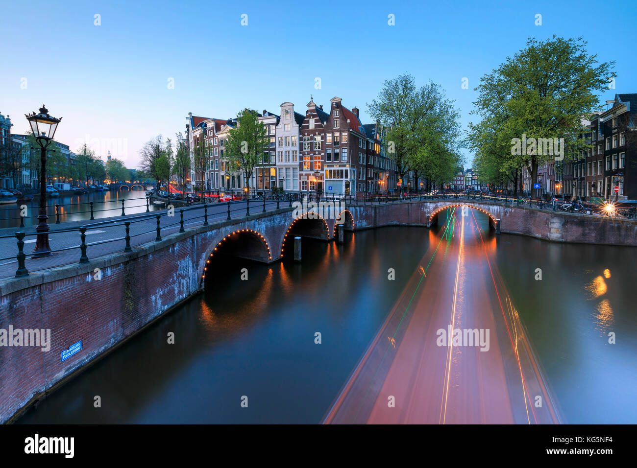 Dusk lights on the typical buildings and bridges reflected in a typical canal Amsterdam Holland The Netherlands Stock Photo