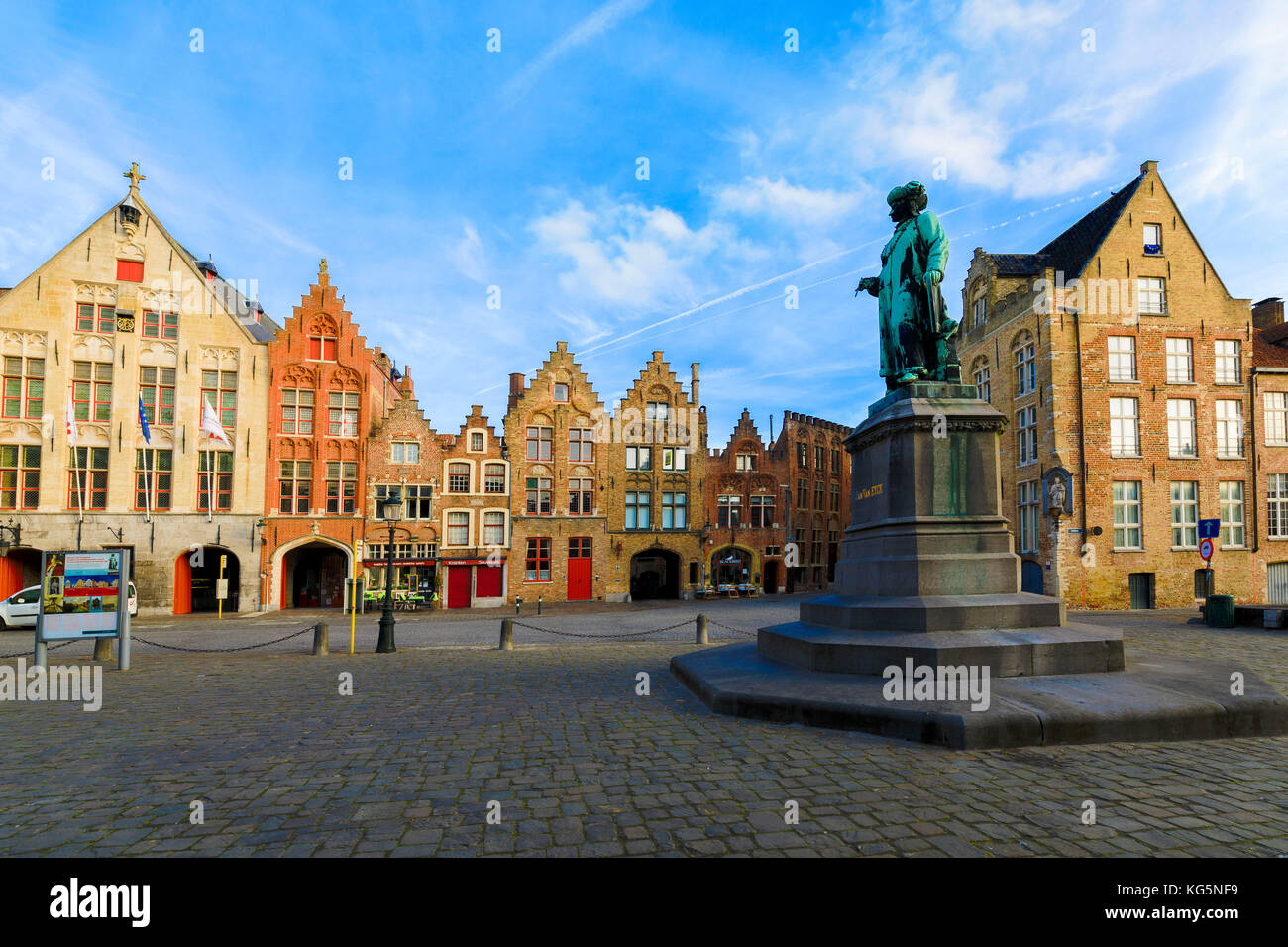 Old statue in the medieval square framed by the typical houses and buildings at dawn Bruges West Flanders Belgium - Stock Image