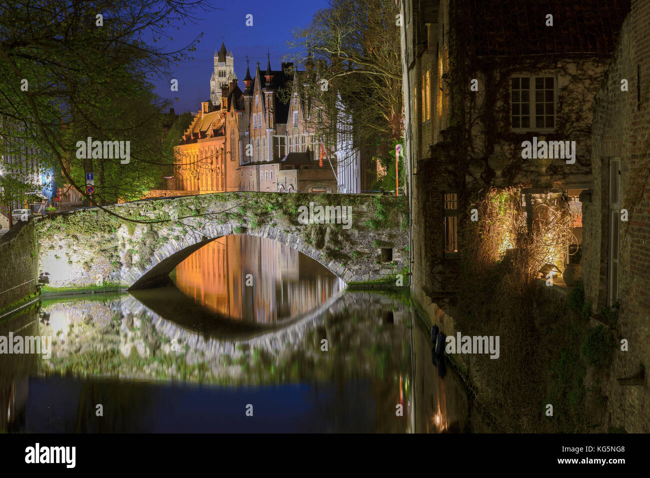 Night view of the medieval buildings of the city centre reflected in the typical canal Bruges West Flanders Belgium - Stock Image