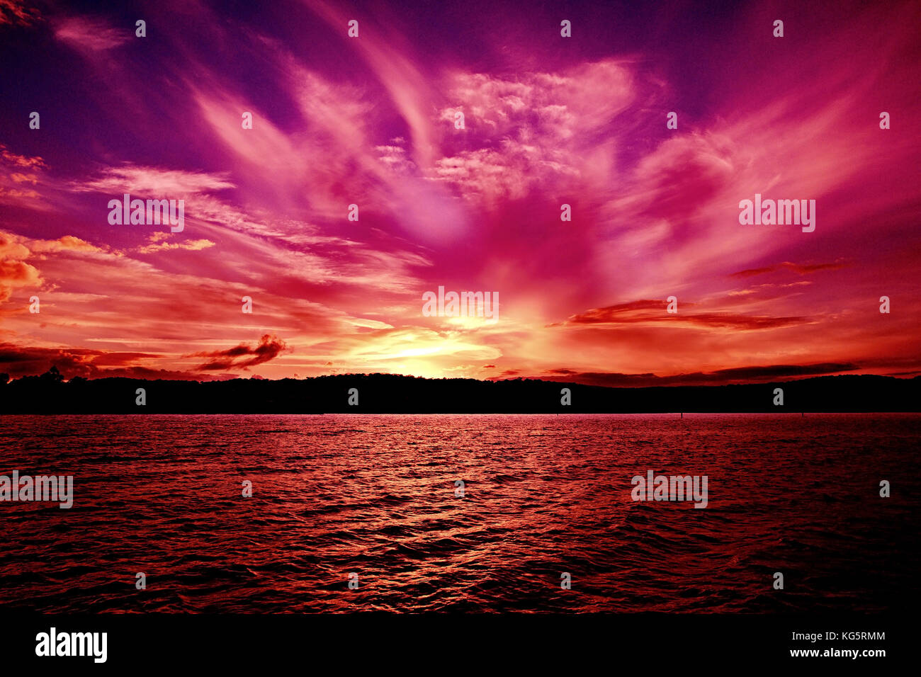 Spectacular vivid pink Orange Violet Ocean Sunset with water reflections. Photographed in Lake Macquarie, NSW, Australia. - Stock Image