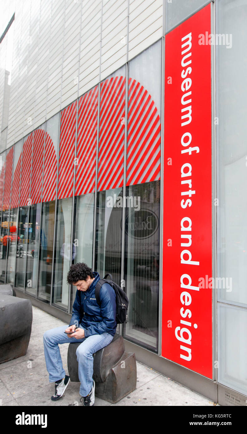 Young man is looking at his smartphone while sitting by the Museum of Arts and Design in NYC. - Stock Image