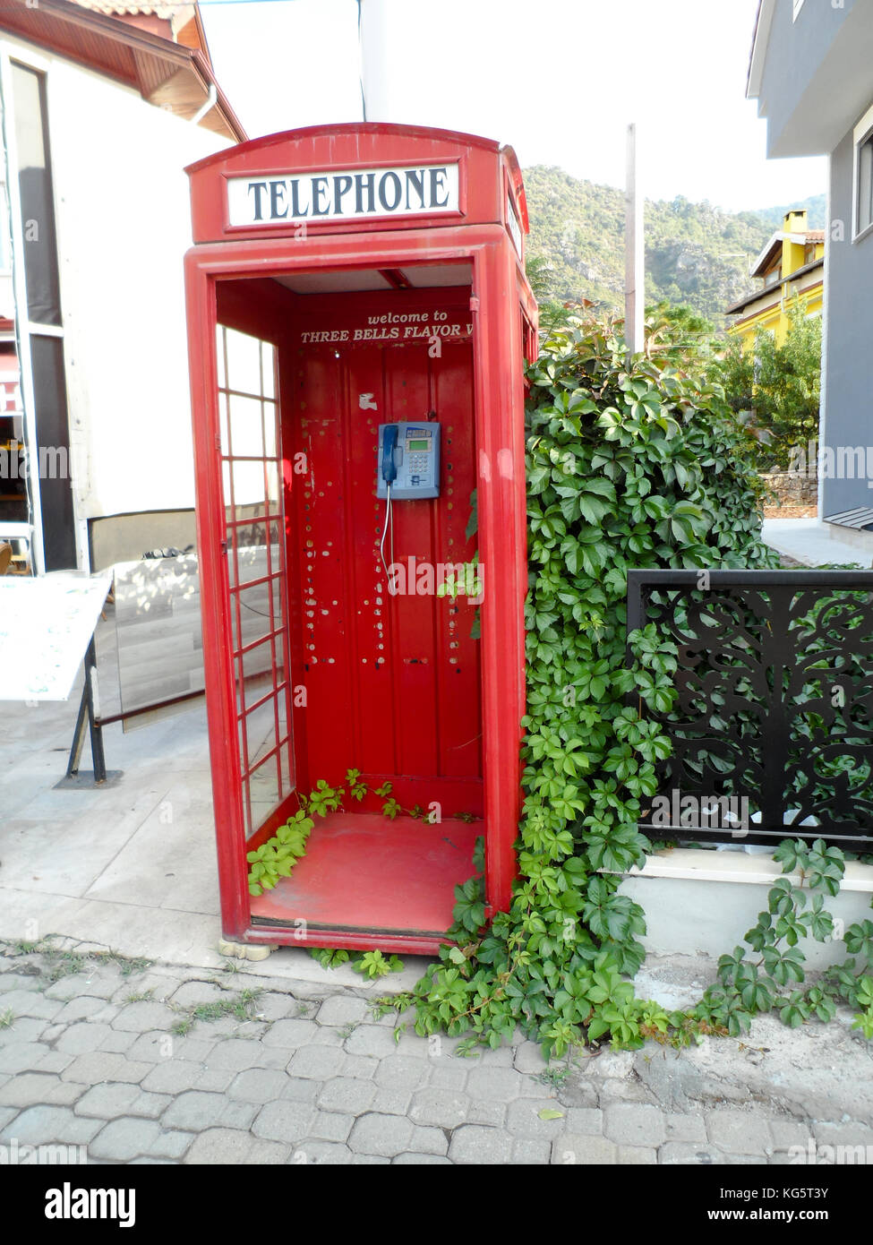 Old replica British red telephone box used as a tourist attraction outside a bar in Icmeler, Mugla province, Turkey - Stock Image
