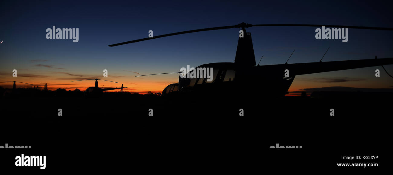 Robinson Helicopters as the sun sets, Sywell - Stock Image