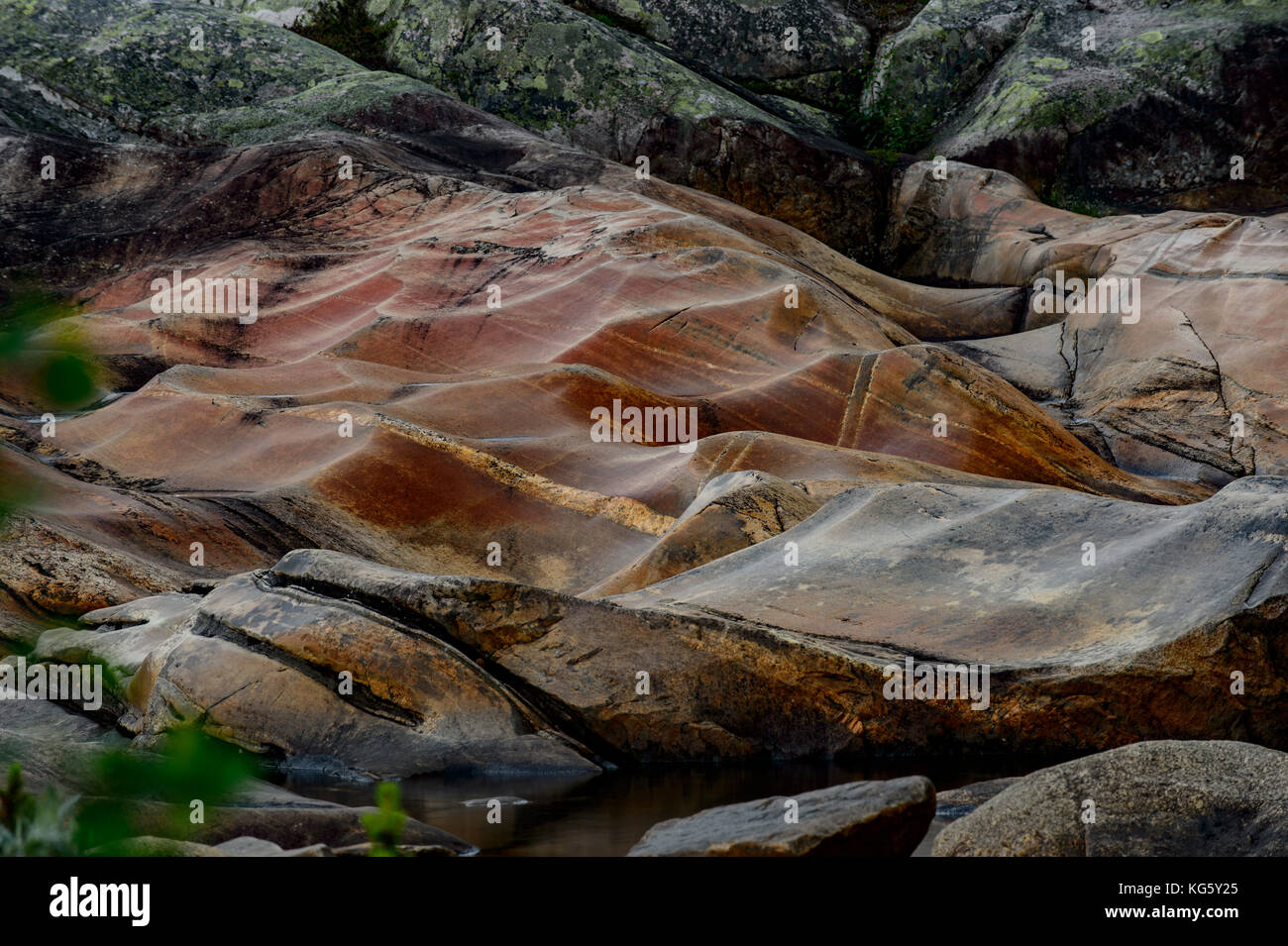 Red rocks in a river bed in the Otra river in Setesdal, Norway Stock Photo