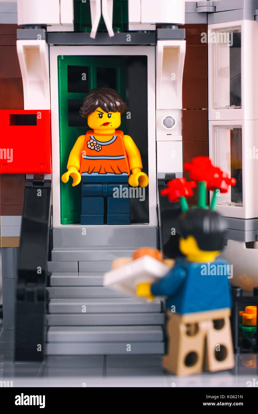 Tambov, Russian Federation - October 18, 2017 Lego angry girl on the porch looking at man with flowers and gift. - Stock Image