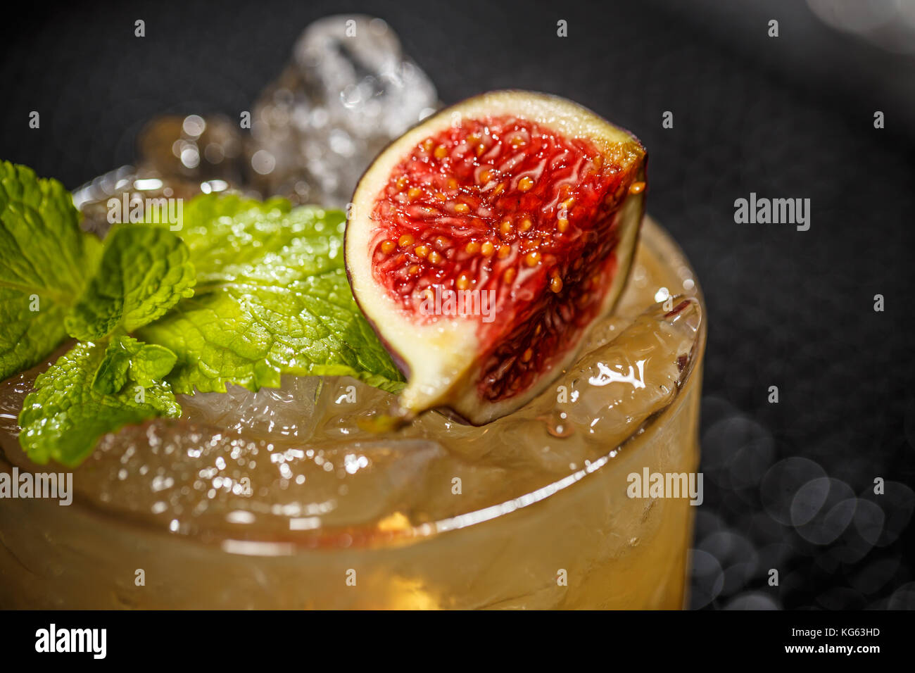 Close up of glass with iced refreshing cocktail with fig and mint leaf - Stock Image