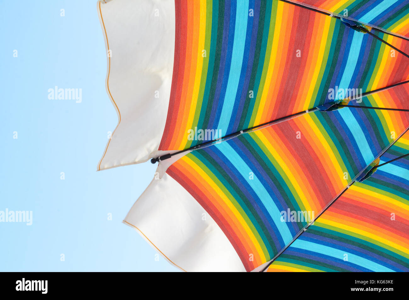 beach umbrellas with rainbow colors, open to protect from the sun Stock Photo