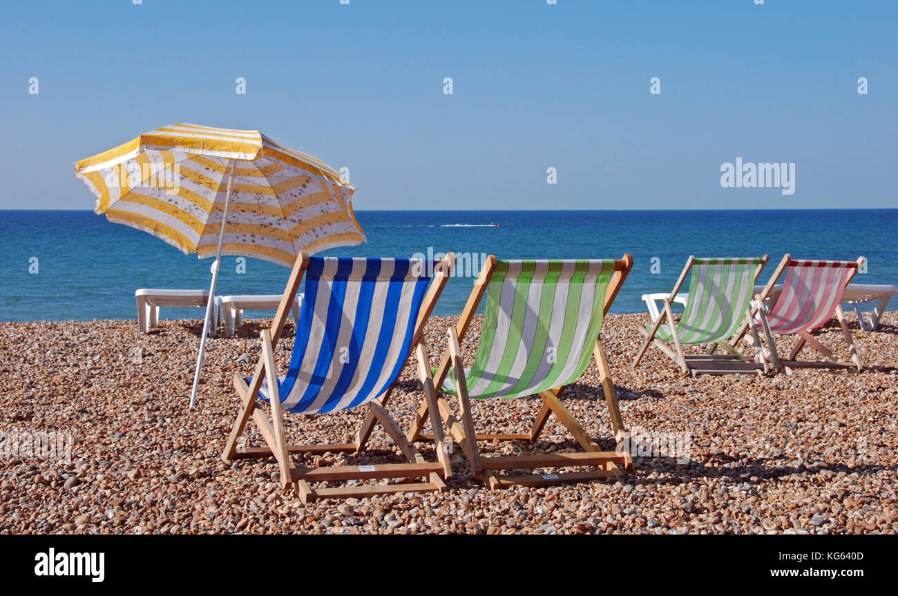 A row of empty deck chairs under a blue sky on a pebble beach with a weather stained beach umbrella by the chair - Stock Image