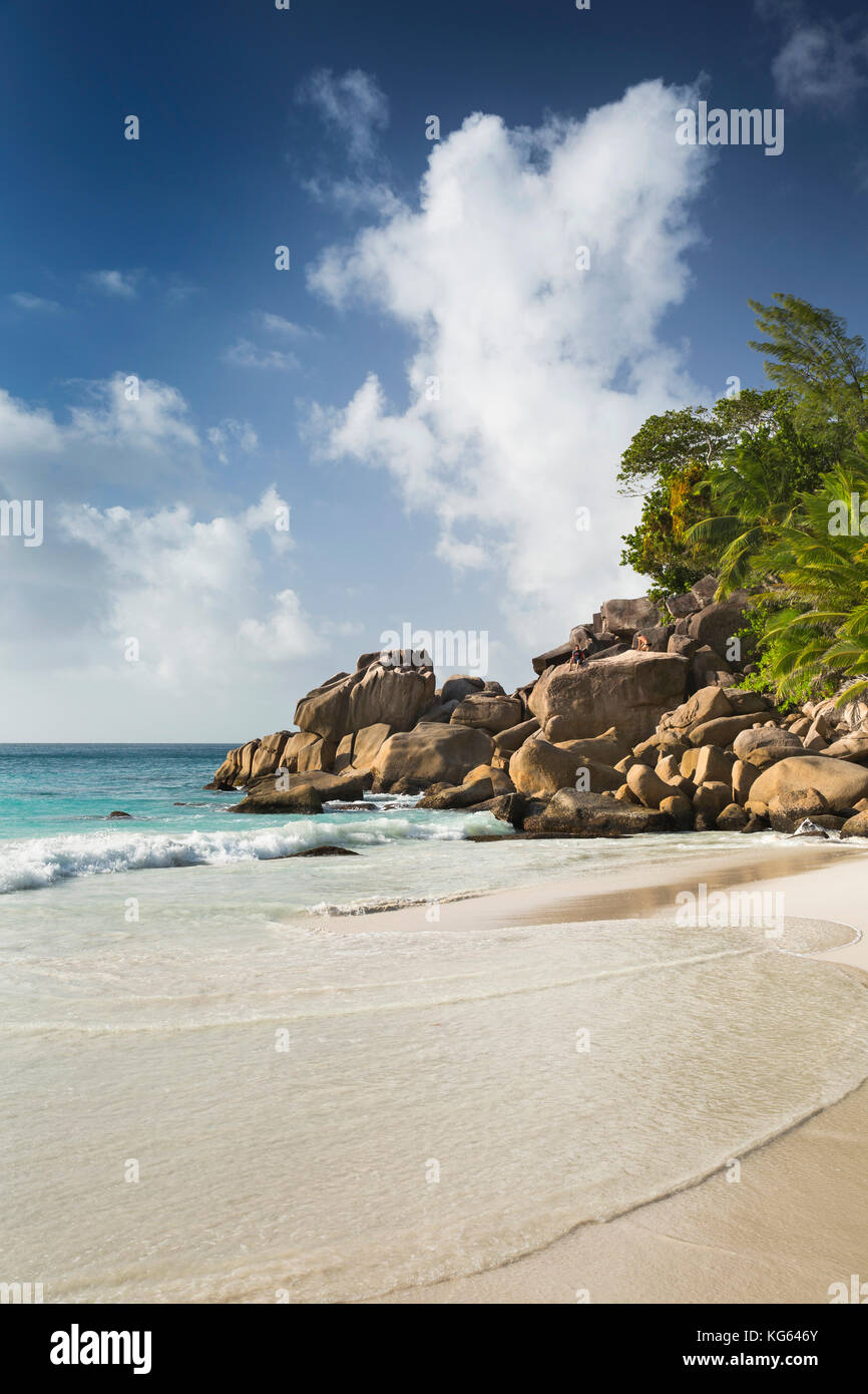 The Seychelles, Praslin, Anse Georgette, beach man sat on rocks at edge of beach - Stock Image