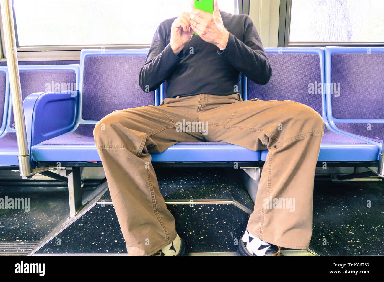 Man Hogging More than One Seat (man spreading) on New York City Bus, NYC, USA - Stock Image