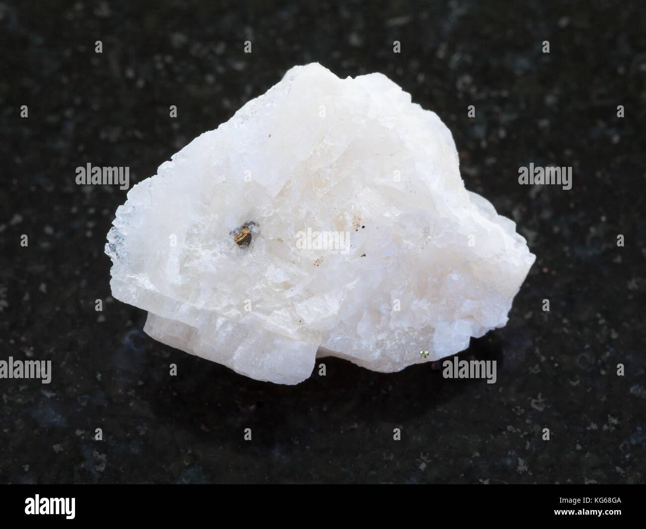 macro shooting of natural mineral rock specimen - rough Baryte stone on dark granite background - Stock Image