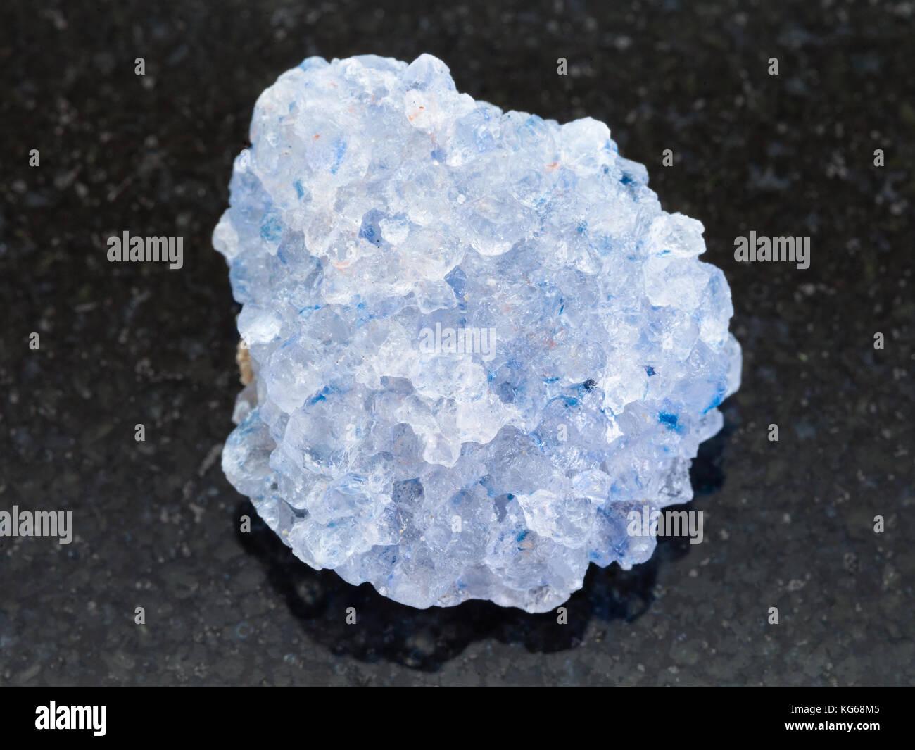 macro shooting of natural mineral rock specimen - rough celestine stone on dark granite background - Stock Image