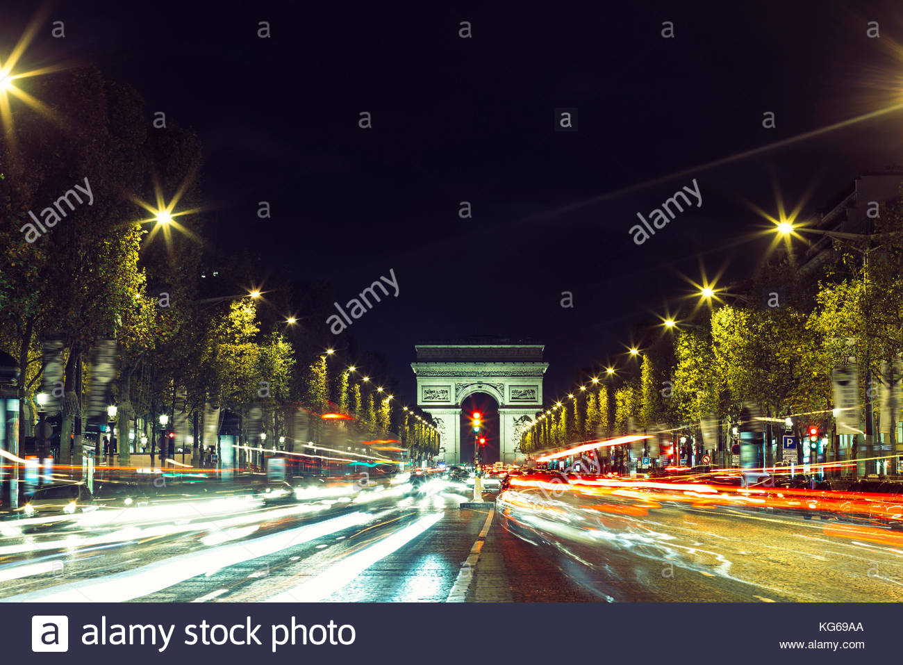 Illuminated Arc de Triomphe and the avenue Champs-Elysees in Paris. Famous touristic places and transportation concept. - Stock Image