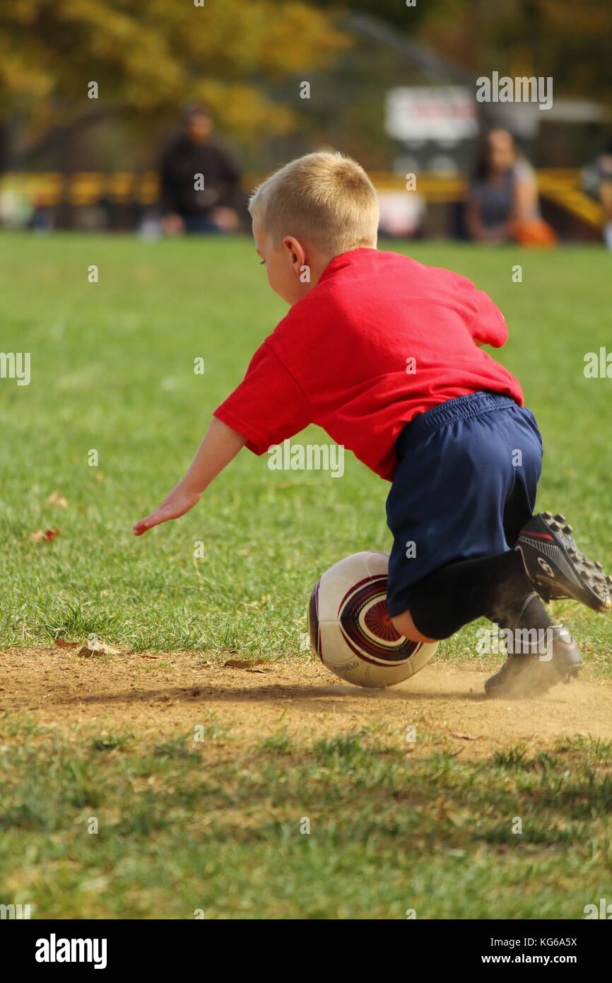 Little boy taking a fall on the soccer field Stock Photo