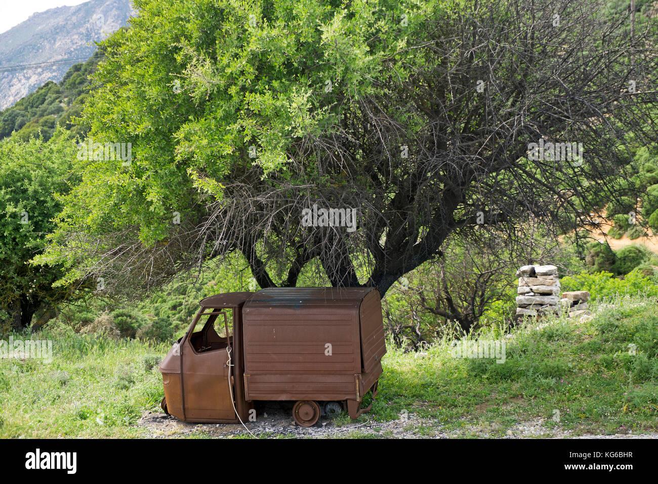 Car wreck under a tree at a road, Naxos island, Cyclades, Aegean, Greece Stock Photo