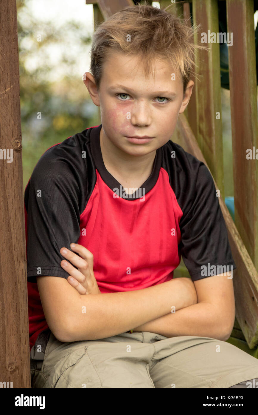 Sad pre-teen boy sitting outside on a climbing frame - Stock Image