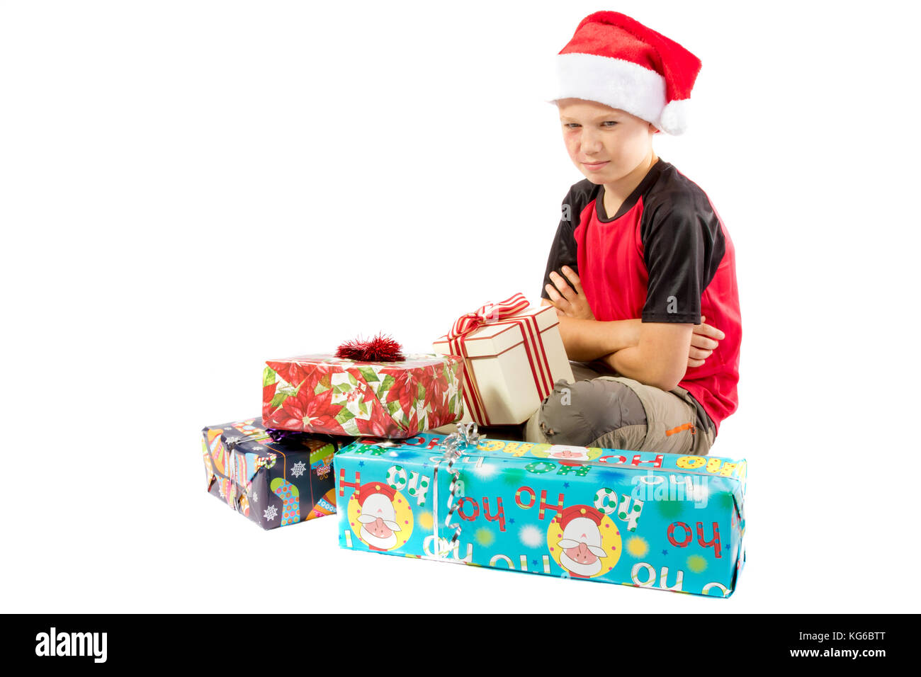 Sulking pre-teen boy with a pile of christmas gifts - Stock Image