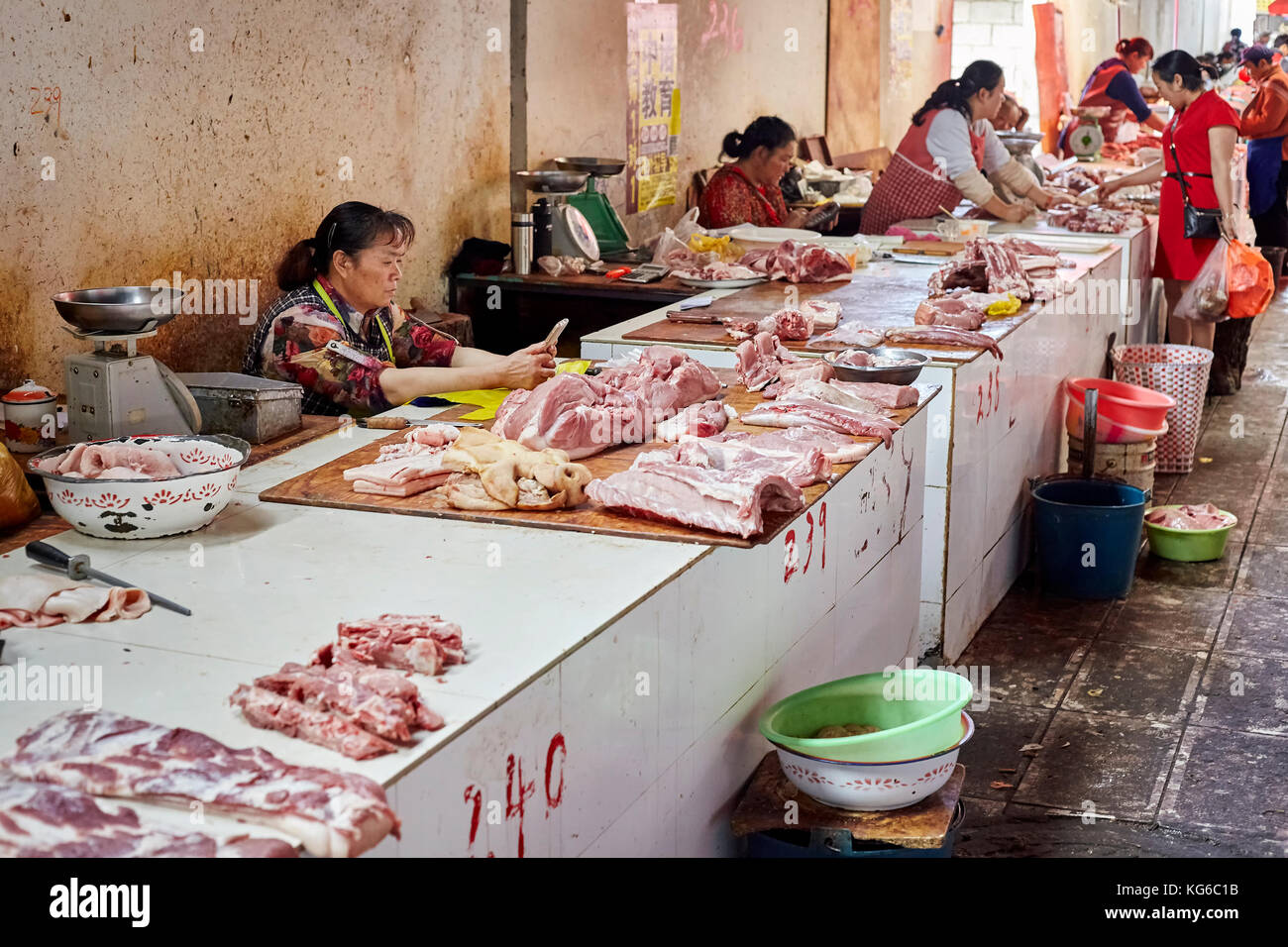 Lijiang, Yunnan, China - September 27, 2017: Women sell fresh meat at the local market. Stock Photo
