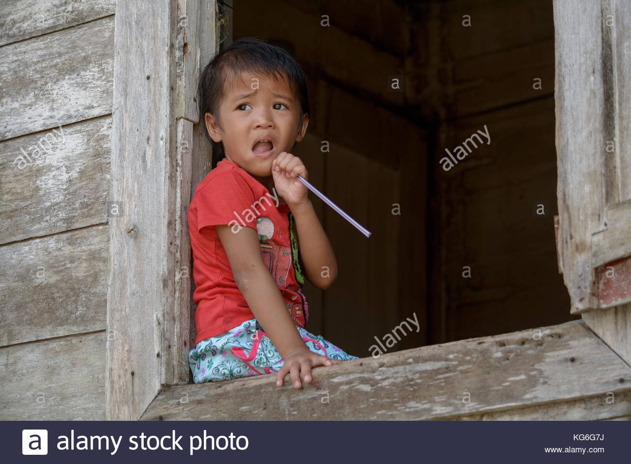A Portrait Of Dayaknese Kid Sitting At Window - Stock Image