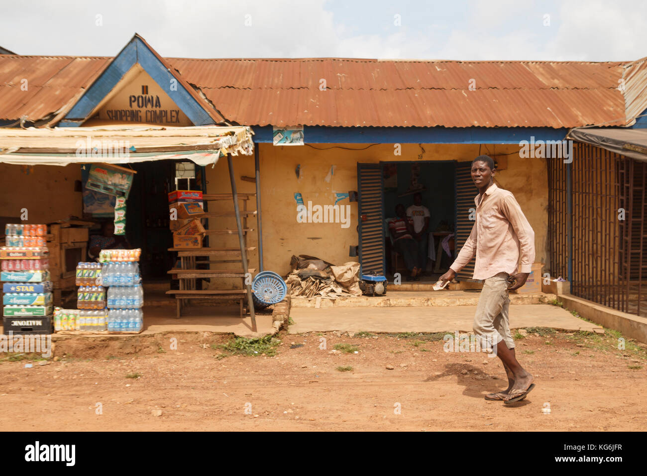 LAGOS, NIGERIA - JULY 25, 2012: Local store with different drinks in Lagos, and nigerian man walking in the street - Stock Image