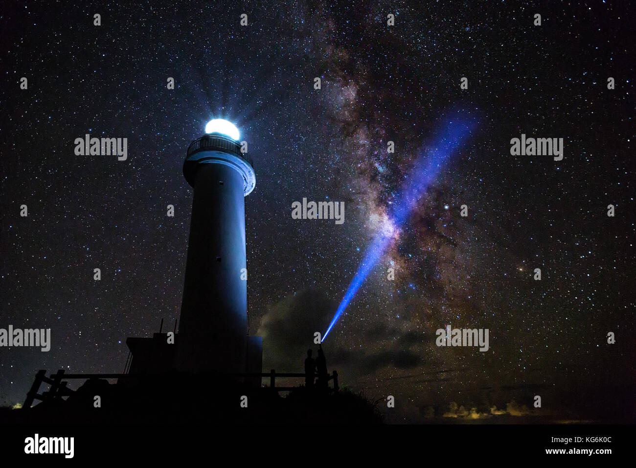 The Milky Way on a clear night with the Uganzaki Lighthouse in the foreground and a laser light shining up into - Stock Image