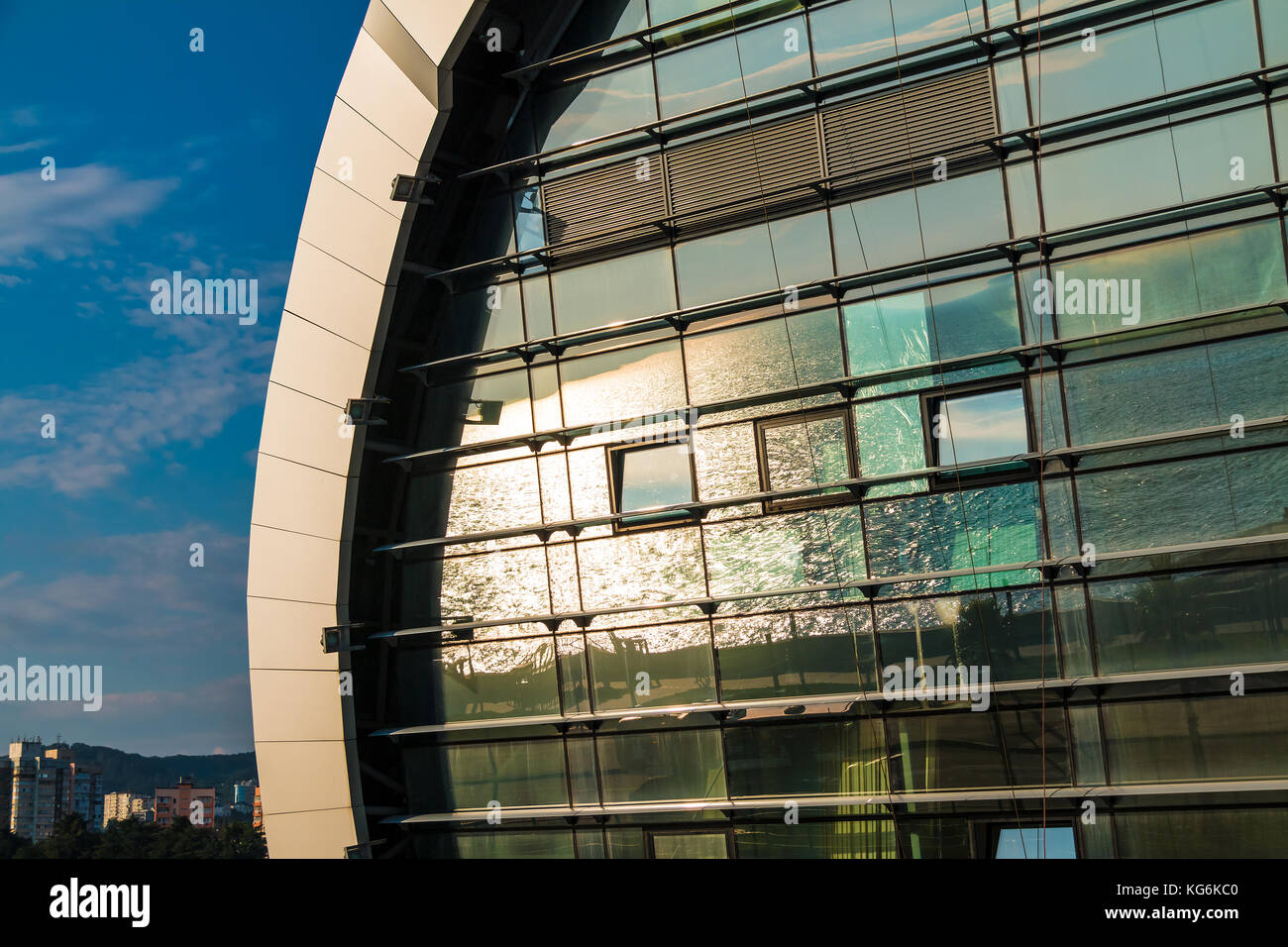Reflection of sea with sun glares seen in the glass facade of railway station in Adler, Russia - Stock Image