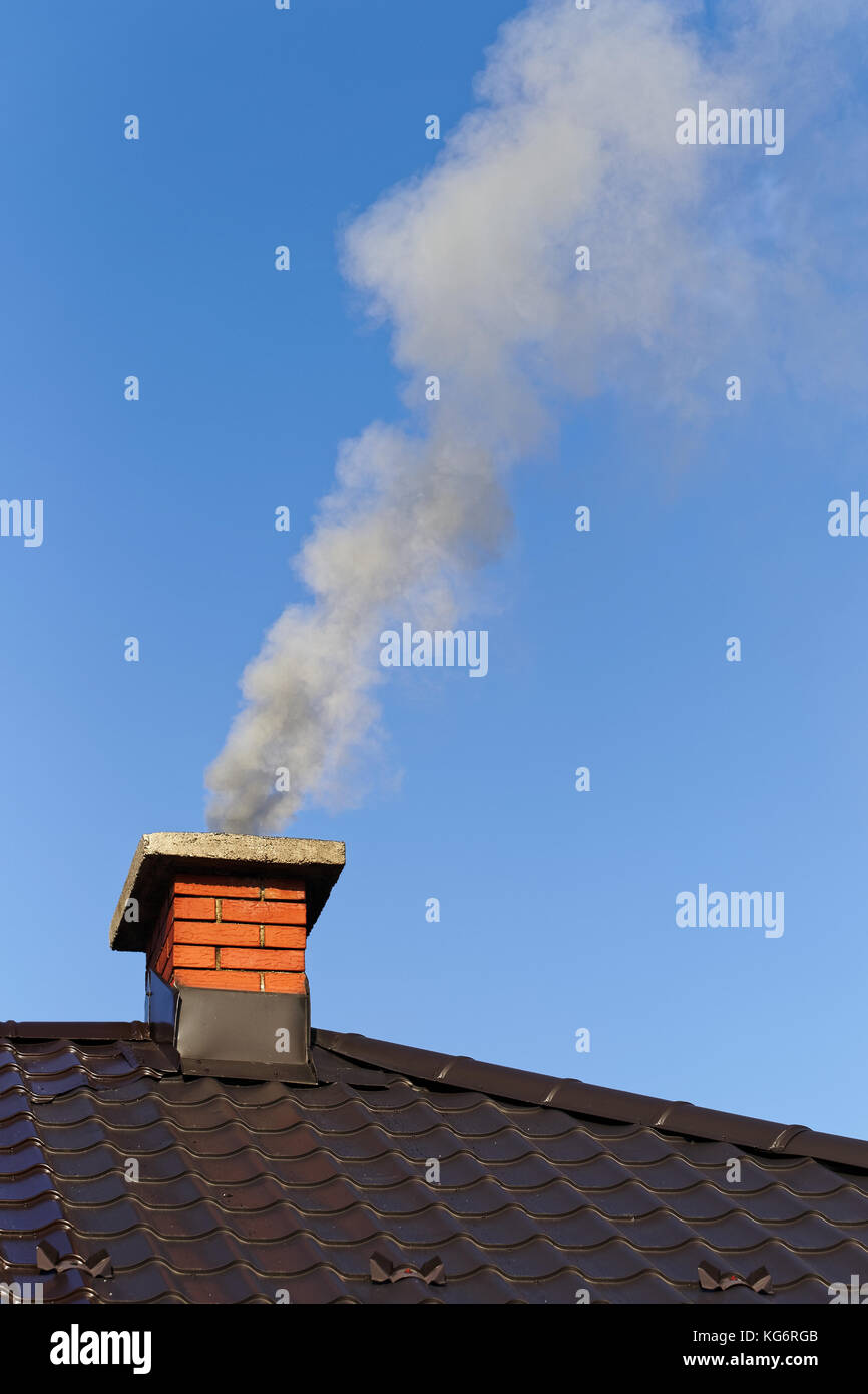 Smoke from brick chimney on the roof against the blue sky Stock Photo
