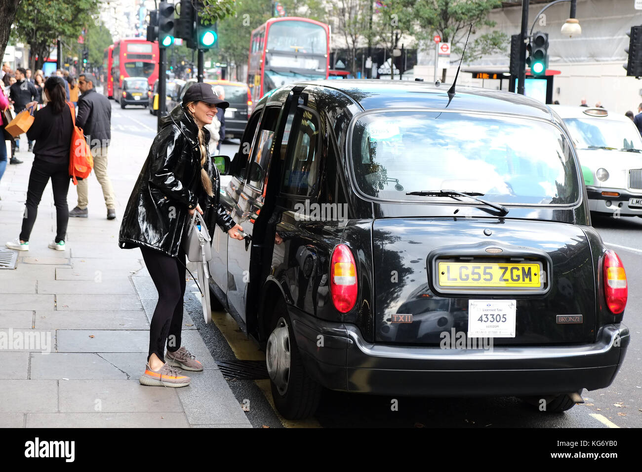 Hailing a traditional Black Cab in London outside Selfridges on Oxford Street Central London UK Stock Photo