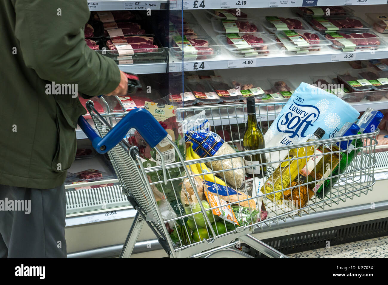A man with a shopping trolley full of groceries at a Tesco supermarket, choosing meat, Scotland, UK - Stock Image