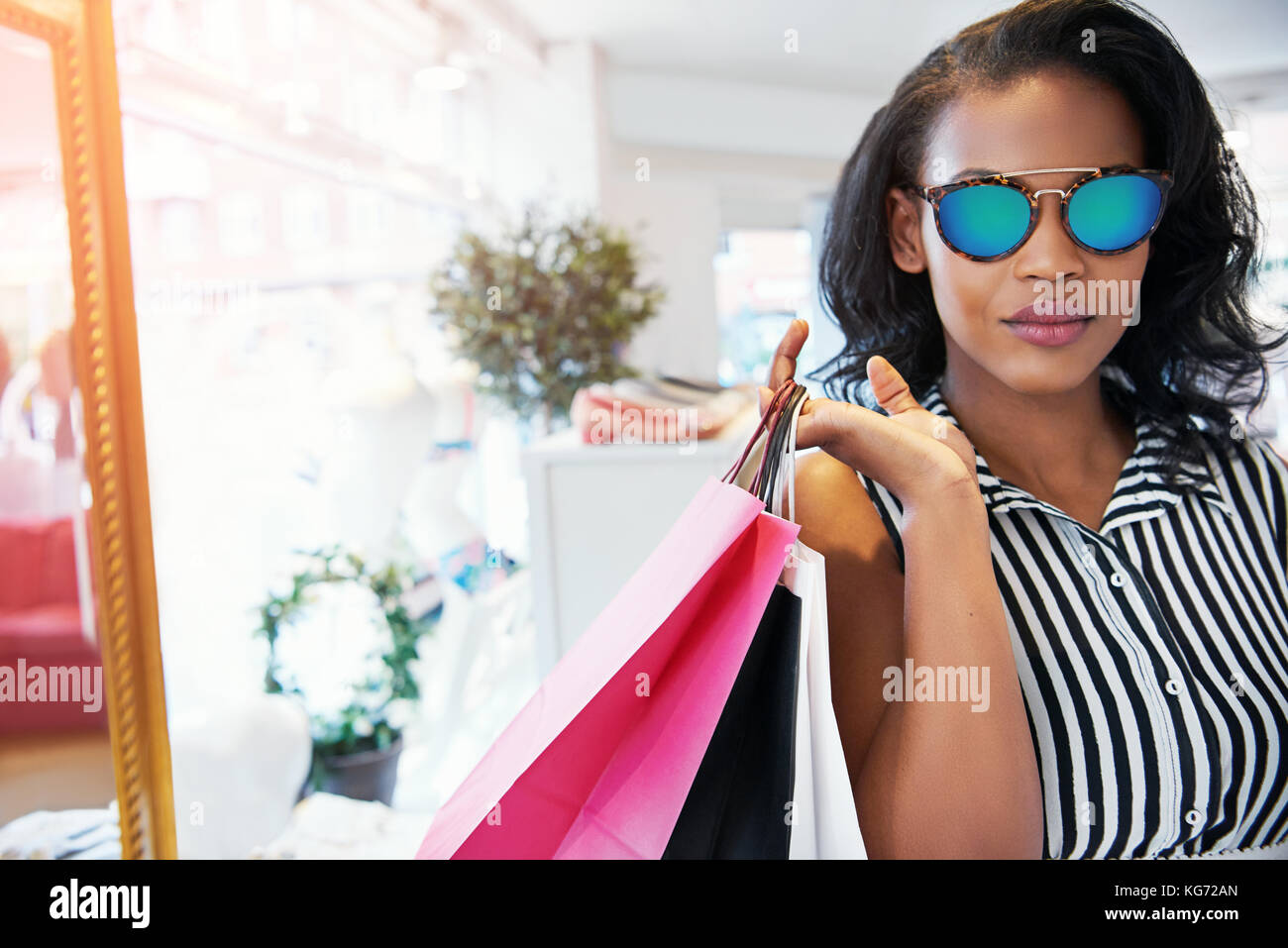 6cb9c70ea8 Gorgeous African female shopper in striped blouse holding bags with calm  expression - Stock Image